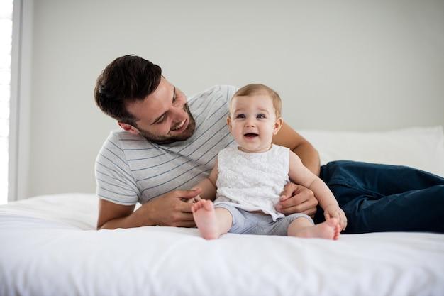 Vader spelen met zijn babymeisje in de slaapkamer thuis