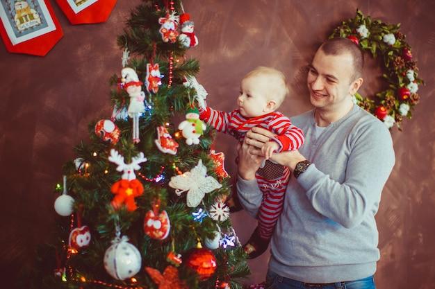 Vader staat met een zoontje voor de kerstboom