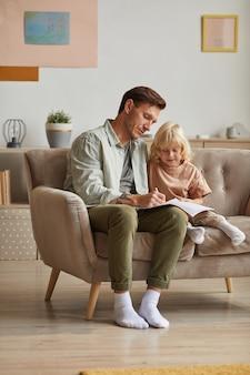 Vader tekent een foto in notitieblok met zijn zoontje dat leert tekenen, zittend op de bank in de kamer