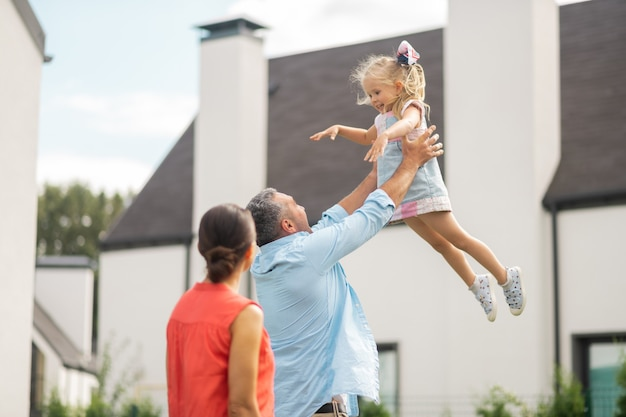 Vader tillen meisje. mooie schattige aantrekkelijke dochter die zich geweldig voelt terwijl vader haar optilt