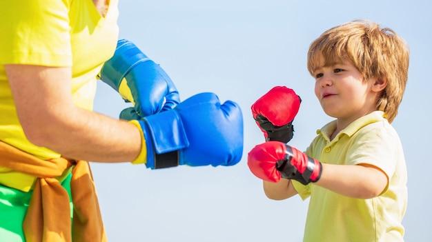 Vader traint zijn zoon boksen. kleine jongen sportman bij bokstraining met coach. kleine jongen die boksoefening doet met grootvader.