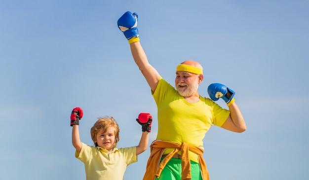 Vader traint zijn zoon boksen. kleine jongenssportman bij bokstraining met coach.