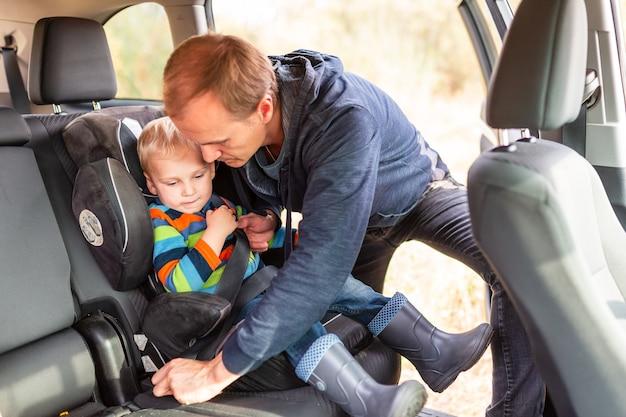 Vader veiligheidsgordel voor zijn babyjongen in zijn autostoeltje.
