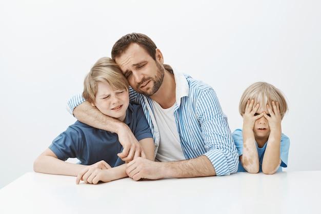 Vader verdriet met zonen zittend aan tafel, jongen knuffelen en huilen, boos en ongelukkig zijn terwijl jongere zoon niets te doen heeft