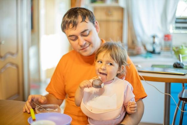 Vader voedende baby zittend op zijn handen thuis. alleenstaande vader. schattige peuter die ijs eet