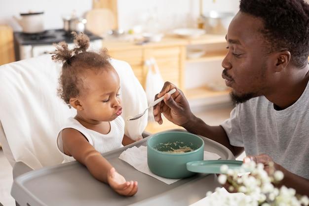 Vader voedt zijn kleine meisje in de keuken