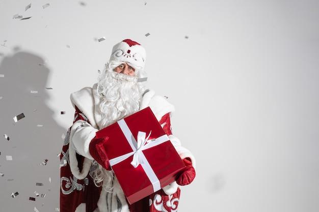 Vader vorst in lange warme jas, rode wanten en een hoed houdt een kerstcadeau met veel confetti om hem heen