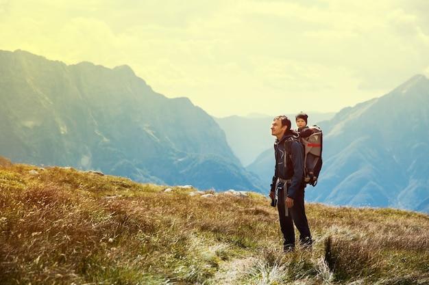Vader wandelen met kind in drager rug op de achtergrond van bergen
