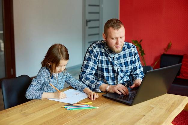 Vader werkt in zijn kantoor aan huis op een laptop, haar dochter zit naast haar en tekent