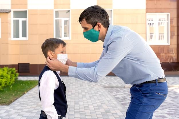 Vader zet een masker op een schooljongen tijdens een pandemie
