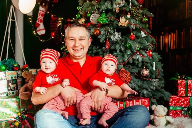 Vader zit met een tweeling in rode pakken voor een kerstboom