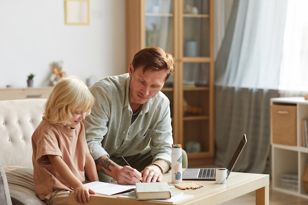 Vader zit met zijn zoon aan tafel en leert hem dat ze thuis in de huiskamer zijn Premium Foto