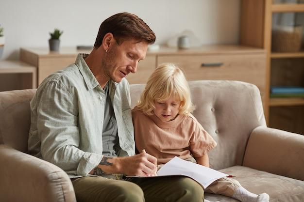Vader zit op de bank met zijn zoontje en leert hem tekenen in de kamer