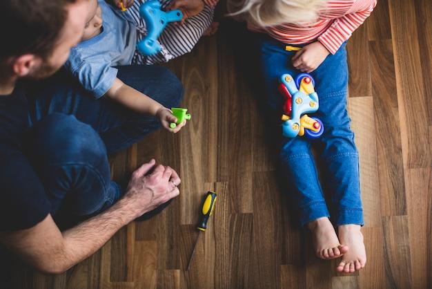 Vader zittend op de vloer met zijn kinderen