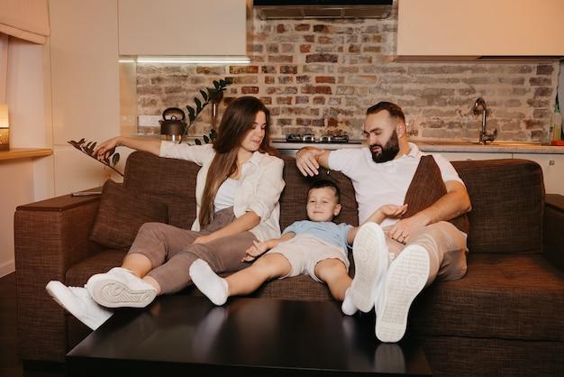Vader, zoon en moeder kijken naar saaie tv-programma's op de bank in het appartement