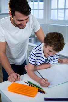 Vader zoon helpen met huiswerk