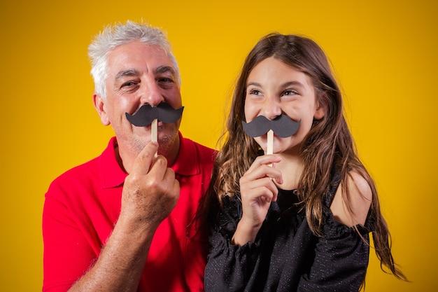 Vaderdag. gelukkige dochter met een kleine papieren snor met haar vader op gele achtergrond. dochter en vader met snor op vakantie Premium Foto