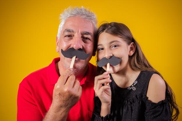 Vaderdag. gelukkige dochter met een kleine papieren snor met haar vader op gele achtergrond. dochter en vader met snor op vakantie