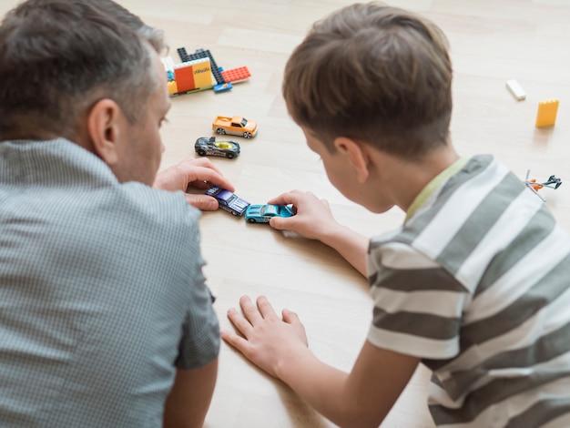 Vaderdag vader en zoon spelen met auto's op de vloer