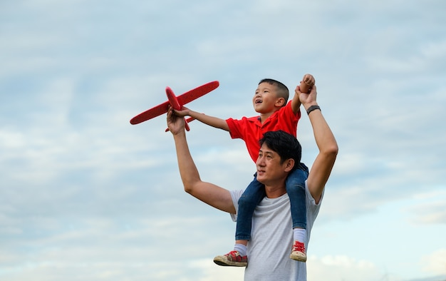 Vaderdag. vader en zoontje spelen samen buiten papieren vliegtuigje