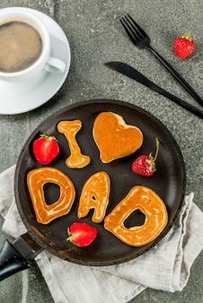 Vaderdag vieren. ontbijt. het idee voor een stevig en heerlijk ontbijt: pannenkoeken in de vorm van felicitaties - ik hou van papa. in een koekenpan, koffiemok en aardbeien. bovenaanzicht copyspace