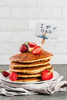Vaderdag vieren. ontbijt. het idee voor een stevig en heerlijk vakantieontbijt: pannenkoeken met boter, ahornsiroop en verse aardbeien, met felicitaties. koffiekop. copyspace