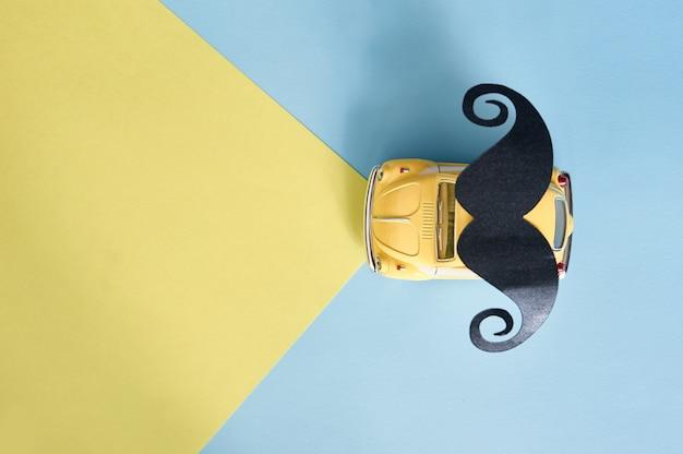 Vaderdag wenskaart met gele speelgoedauto en zwart papier snor