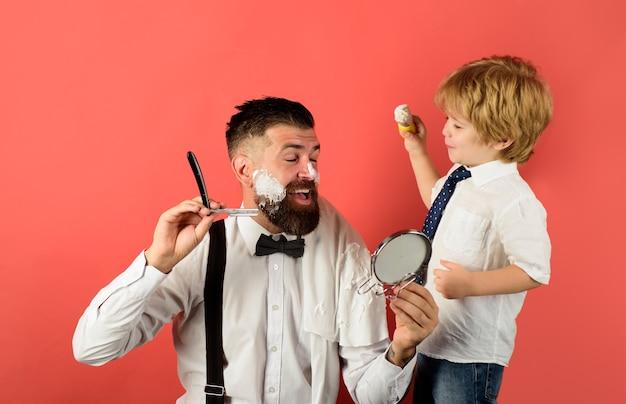 Vaderdagassistent voor vader kleine jongen houdt spiegel vast voor vader kapper die bebaarde man scheert