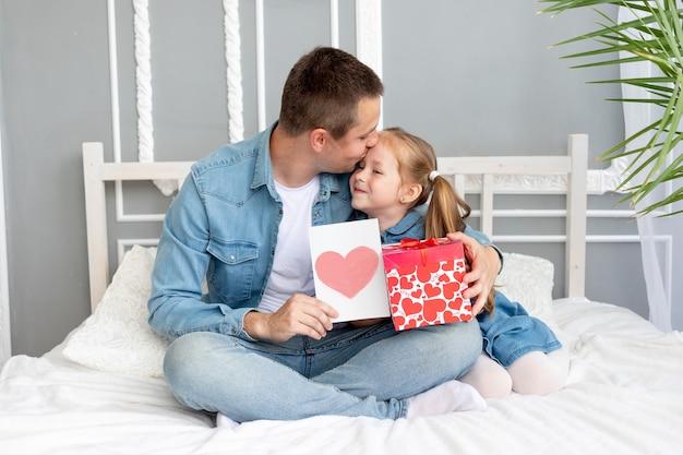 Vaderdagconcept een meisjesdochter geeft haar geliefde vader een geschenk en een hartkaart, het concept van gelukkig vaderschap en een vakantie