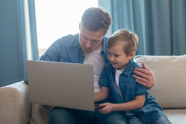 Vaderdagpapa en zoon die laptop bekijken