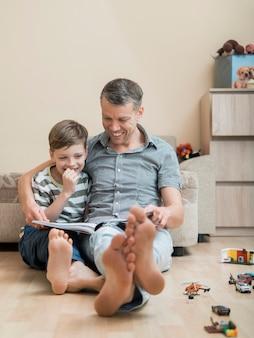 Vaderdagvader en zoon die een boek op de vloer lezen