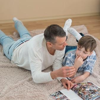 Vaderdagvader en zoon die een hoge mening van het stripboek lezen