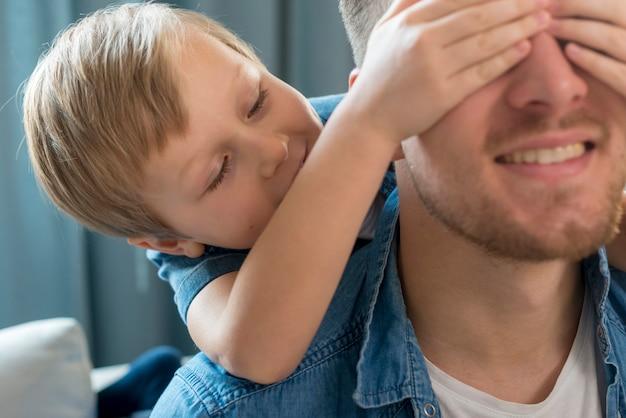 Vaderdagzoon die de ogen van zijn vader bedekt