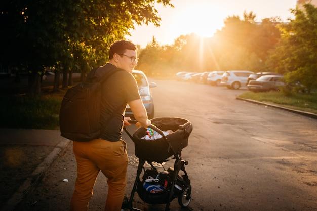 Vaderpapa met pasgeboren kinderwagenwandelwagen buiten tijdens de zonsondergang van de de zomeravond