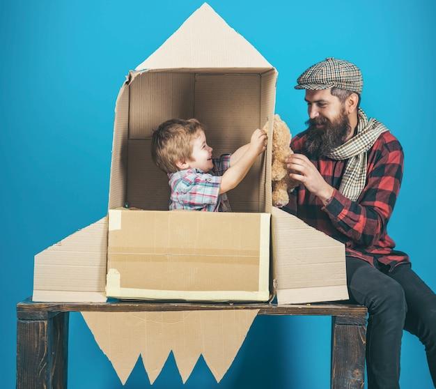 Vaders dag gelukkige familie spelen met kartonnen raket kosmonaut concept schattige jongen spelen kosmonaut