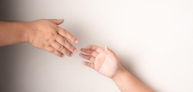 Vaders hand om de hand van een kind met het syndroom van down vast te houden