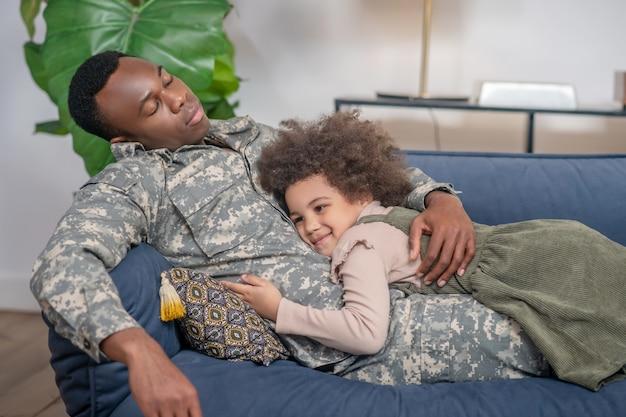 Vaderschap. donkere jonge, vermoeide militaire man met gesloten ogen en knuffelende gelukkige dochter die thuis op de bank ligt