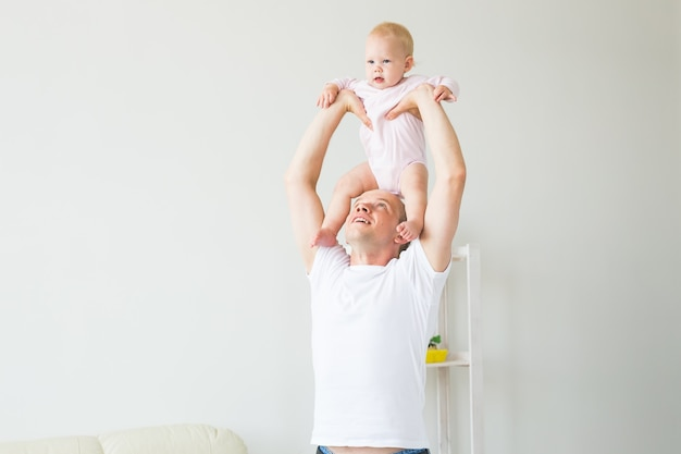 Vaderschap en gezin concept - vader en kleine peuter baby binnenshuis thuis, spelen.