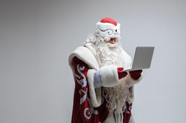 Vadervorst met lange baard doet iets met een laptop, foto geïsoleerd op grijze muur