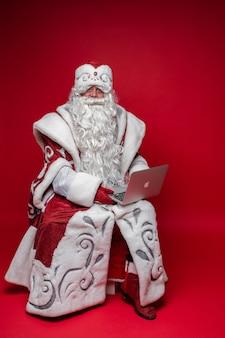 Vadervorst met lange witte baard horende internet, foto geïsoleerd op rode muur