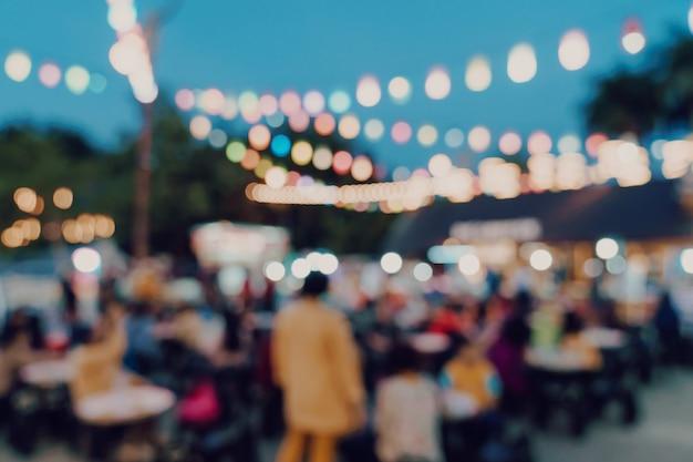 Vage achtergrond bij de mensen die van het de marktfestival van de nacht op weg lopen.