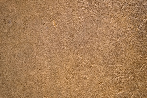 Vage goudbruine de textuurachtergrond van de pleistermuur