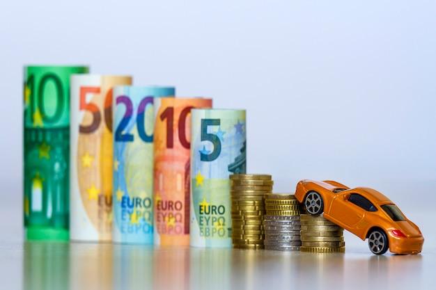 Vage rij van gerolde honderd, vijftig, twintig, tien en vijf nieuwe eurobankbiljetten en stapel munten met gele speelgoed dure sportwagen.