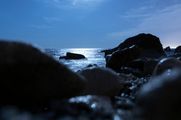 Vage rotsen in het water bij nacht