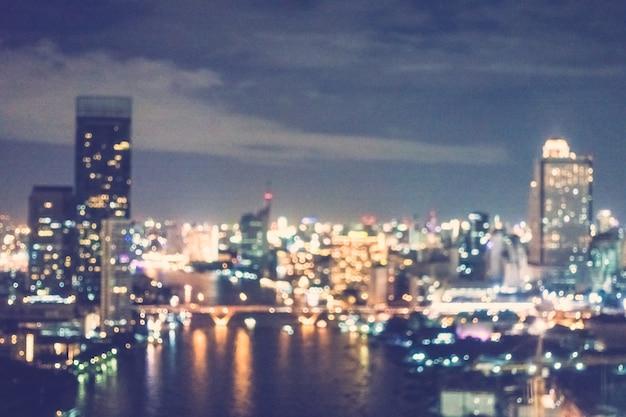 Vage stad met wolkenkrabbers en een rivier bij nacht