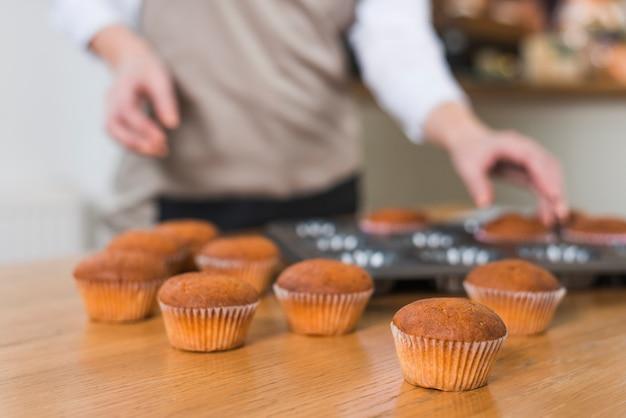Vage vrouwelijke bakker die muffins verwijdert uit het dienblad op houten geweven lijst