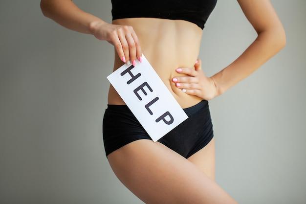 Vaginale of urinaire infectie en problemen. jonge vrouw houdt papier met sos boven kruis