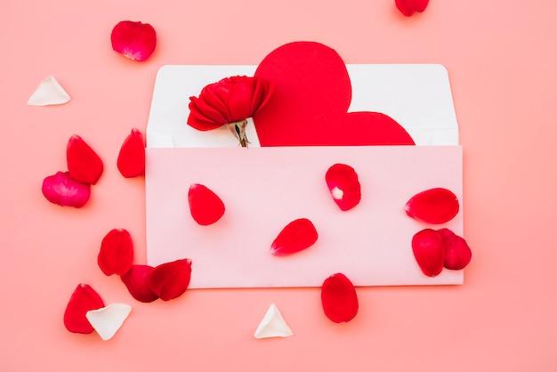Vak met papieren hart en bloem in de buurt van bloemblaadjes