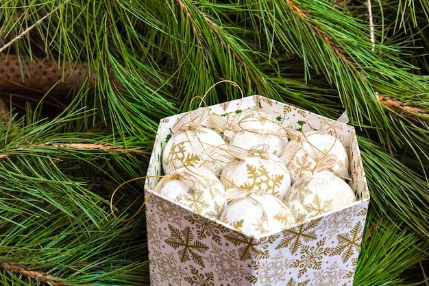 Vak met witte kerstballen op de achtergrond van de kerstboom