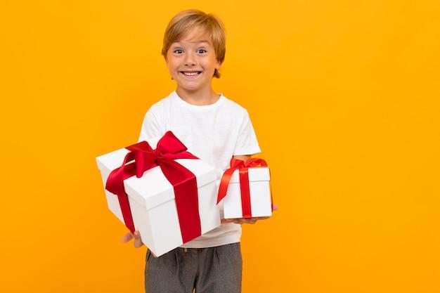 Vakantie. aantrekkelijke jongen steekt een doos met een geschenk met een rood lint op een fel geel